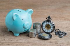 Blue piggy bank and coins stacked and pocket watch on wood table Royalty Free Stock Image