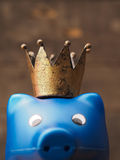 Blue piggy bank with a crown. Blue piggy bank with an old crown, saving money concept with selective focus on the crown Stock Photo