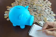 Blue piggy bank and hand writing on notepad Royalty Free Stock Photo
