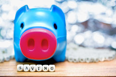 Blue piggy bank with Saving message on green background Stock Image
