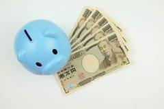 Blue piggy bank standing on banknote, Japanese money, money savi Stock Photos