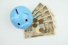 Blue piggy bank standing on banknote, Japanese money, money savi Royalty Free Stock Photo