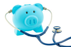 Blue piggy bank with stethoscope isolated on white background. Royalty Free Stock Photos