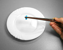 Blue pill. And chopsticks on a white plate Stock Photos