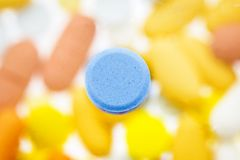Blue pill with defocus background Royalty Free Stock Photo