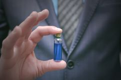 Blue pill essential oil in male hands. Right choice of medicaments. Blue pill essential oil in male hands. Presentation of new drug pill or steroid concept Stock Photography