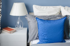 Blue pillow on bed with glass lamp on white table in modern blue Royalty Free Stock Photography