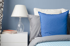 Blue pillow on bed with glass lamp on white table in modern blue Stock Photography