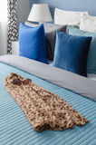 Blue pillow on bed with glasses on cloth in modern bedroom Royalty Free Stock Photography