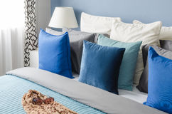 Blue pillow on bed with glasses on cloth in modern bedroom Stock Photo