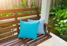 Blue pillow Placed on a wooden swing in the resort. Royalty Free Stock Photos