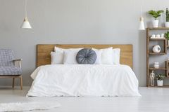 Blue pillow on white bed with wooden headboard in bedroom interior with armchair. Real photo stock photo