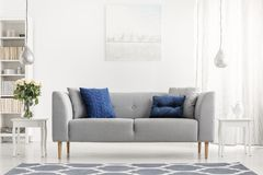 Blue pillows on grey couch next to table with flowers in white flat interior with painting. Real photo. Blue pillows on grey couch next to table with flowers in stock photography