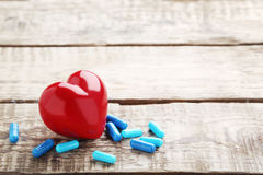 Blue pills capsule. Heap of blue pills capsule with red heart on wooden table Royalty Free Stock Photos