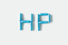 Blue Pills capsules in shape of word HP. Life concept isolated. Royalty Free Stock Image