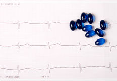 Blue pills on ECG chart (electrocardiogram) Stock Image