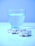 Blue pills and glass of water Royalty Free Stock Photography