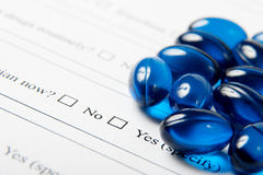 Blue pills on medical questionnaire Stock Photos