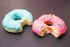 Blue and pink bitten donut Stock Images