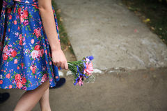 Blue and pink bouquet of wildflowers in the hand of woman Stock Photos
