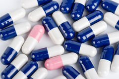 Blue and pink capsule pills. On white Royalty Free Stock Photo