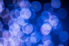 Blue and pink Christmas tree bokeh on black background of defocused glittering lights, Christmas background pattern concept royalty free stock image