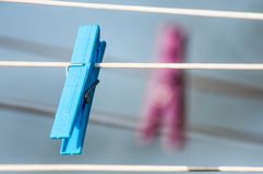 Clothespins on a washing line. Blue and pink clothespins on a washing line Stock Images