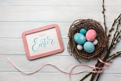 Blue and pink colored eggs in nest and willow. Easter greeting card. Top view with space for your greetings stock photography