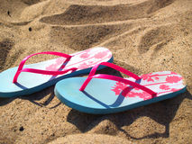Blue and pink flip flops on sandy beach Stock Photo