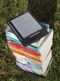 Blue Pink Gray and Green Labeled Hardbound Book Pile on Green Grass during Daytime Royalty Free Stock Photography