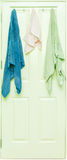 Blue, Pink and Green towel hang on a wooden door. Royalty Free Stock Photos