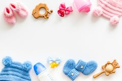 Blue and pink knitted footwear, hat, dummy, rattle and bottle frame for baby on white background top view mockup