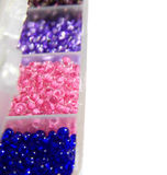 Blue, pink, lilac beads in boxes, closeup Royalty Free Stock Photo