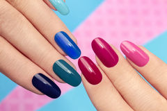 Blue pink manicure. Blue pink nail Polish on long nails on a colored background Royalty Free Stock Photography