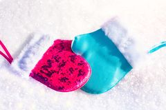 Blue and pink mittens on the snow in an embrace. Christmas toys. Male and female. Blue and pink mittens on the snow in an embrace. Christmas toys. Male and Royalty Free Stock Image