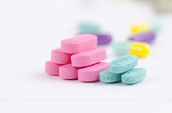 Blue and pink piles of tablet. Two set of pink and blue tablets arranged in separate piles on white background Royalty Free Stock Images