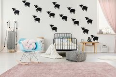 Blue and pink spacious bedroom. Blue rocking chair on pink carpet in spacious bedroom interior with pouf next to bed against white wall with black sheep stickers stock photo