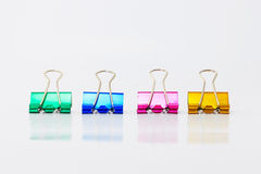 Blue, pink, yellow and green paperclip. On table Royalty Free Stock Photos