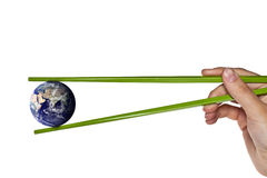 Blue planet earth between green chopsticks Royalty Free Stock Images