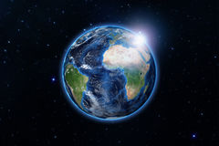 Blue planet earth from space showing America and Africa, USA, globe world with blue glow edge and sun light sunrise on space in a Stock Photography