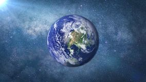 Planet Earth lit by the Sun and the Milky Way galaxy. The blue planet lit by the Sun Stock Photo