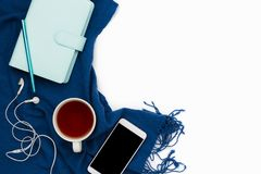 Blue planner, smartphone with headphone and black copyspace screen and cup of tea. Flatlay arrangement with blue planner, smartphone with headphone and black Stock Photography
