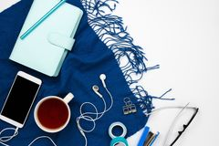 Blue planner, smartphone with headphone and black copyspace screen. Flatlay arrangement with blue planner, smartphone with headphone and black copyspace screen Stock Photo