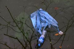 Plastic bag and water bottle in dirty water royalty free stock photo