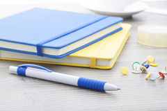 Blue plastic ball pen with office supplies. On wooden table stock photo