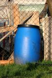 Blue plastic barrel with black top next to wire fence and wooden boards surrounded with uncut green grass in local garden. On warm sunny spring day stock image
