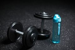 Heavy steel dumbbells, a blue bottle for water, equipment for sports routine on a dark blurred background. Stock Photos