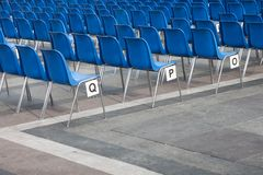 Blue plastic chairs in line Royalty Free Stock Images