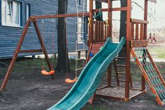 Blue plastic children`s slide on a wooden game complex. Children`s playground without anyone.  stock image