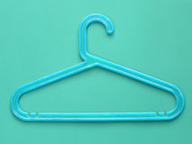 Blue plastic cloth hanger on blue background Stock Photography